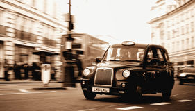 Moving London Taxi. In sepia color Royalty Free Stock Image