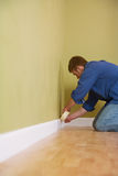 Moving: Man Covers Molding With Tape Before Painting Stock Images