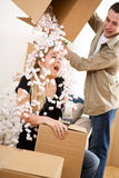 Moving: Man Dumps Box of Peanuts On Wife For Fun Stock Image