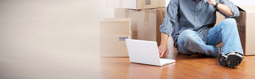 Moving. Man sitting on the floor in new apartment with moving boxes Stock Photography