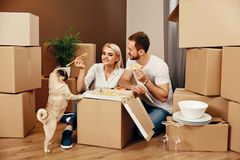 Moving. Man And Woman Eating Near Boxes. Moving. Happy Man And Beautiful Woman Eating Near Cardboard Boxes And Dog In New House. High Resolution stock photos