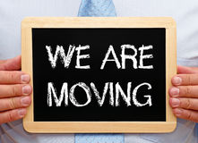 We are moving - Manager holding chalkboard with text. In his hands royalty free stock images