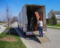 Free Moving Men Unloading A Moving Truck Royalty Free Stock Image - 164690546