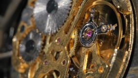 Moving metal gears inside working watch mechanism. Close up stock footage