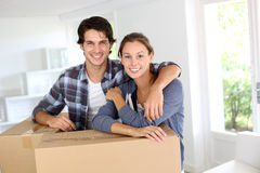 Moving in new home. Smiling couple leaning on boxes in new home Royalty Free Stock Photo