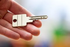 Moving into a new home: Close up of a hand holding a key. Property and real estate. Holding a house key in the hand: New home and property estate owner real rent stock photography