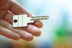 Moving into a new home: Close up of a hand holding a key. Property and real estate. Holding a house key in the hand: New home and property estate owner real rent royalty free stock image