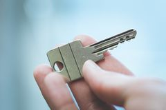 Moving into a new home: Close up of a hand holding a key. Property and real estate. Holding a house key in the hand: New home and property estate owner real rent royalty free stock images