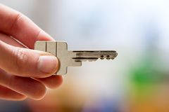 Moving into a new home: Close up of a hand holding a key. Property and real estate. Holding a house key in the hand: New home and property estate owner real rent stock photo