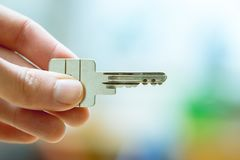 Moving into a new home: Close up of a hand holding a key. Property and real estate. Holding a house key in the hand: New home and property estate owner real rent stock image