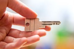 Moving into a new home: Close up of a hand holding a key. Property and real estate. Holding a house key in the hand: New home and property estate owner real rent stock photos