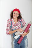 Moving in new house. Woman holding wallpaper rolls for the house Stock Photography