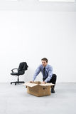 Moving into a new office. Businessman looking around and packing with cardboard box in an empty office Royalty Free Stock Photos