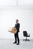 Moving into a new office. Smiling businessman holding a cardboard box and standing in an empty new office Stock Photo