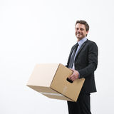 Moving into a new office. Smiling businessman holding a cardboard box and standing into an empty new office Royalty Free Stock Photo