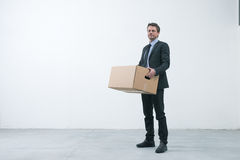 Moving into a new office. Smiling businessman holding a cardboard box and standing into an empty new office Stock Photo