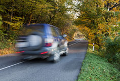 Moving off-road car on the asphalt highway. Blurred fast moving dark car under the trees stock photo