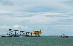 Moving oil rigs, Relocate the oil and gas drilling rig with a towing boat to the Gulf of Thailand stock images