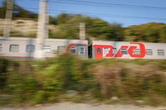The moving passenger train of the Russian Railways, RZHD coming from Adler. Motion blur. RUSSIA, KRASNODAR KRAI, GIZELE-DERE VILLAGE, August 06, 2018: The moving royalty free stock image
