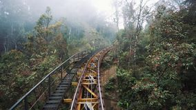 Moving passenger train traveling through a forest railway on mountain hill. Train go to garage. Cloudy weather. Ba Na hills. Danang.Vietnam stock video