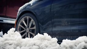 Moving Past Car In The Snow. Ground level tracking shot moving past car with snow in the foreground stock footage