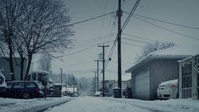 Moving Past Residential Road In Snowfall. Moving over road in alleyway with snow falling stock footage