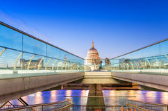 Moving people alonf Millennium Bridge in London. Night view of S. T Paul Cathedral Royalty Free Stock Photos