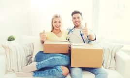 Happy couple with boxes showing thumbs up at home Stock Photo