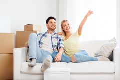 Happy couple with cardboard boxes at new home. Moving, people, repair and real estate concept - happy couple with big cardboard boxes on sofa at new home stock photos