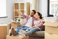Happy couple with boxes moving to new home stock image