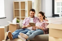 Happy couple with boxes moving to new home. Moving, people, repair and real estate concept - happy couple with photo frame and cardboard boxes sitting on sofa at royalty free stock photos