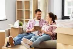 Happy couple with boxes moving to new home stock images