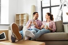 Happy couple drinking coffee moving to new home. Moving, people, repair and real estate concept - happy couple sitting on sofa and drinking coffee at new home royalty free stock photography