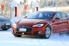 Moving Red Tesla Model S Electric Car in Winter Snow stock image