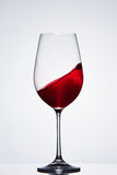 Moving red wine in the pure fragile wineglass standing against light background with reflection. Royalty Free Stock Images