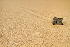 Moving rock on cracked desert ground Royalty Free Stock Photos