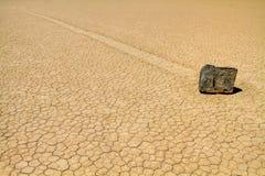 Moving rock on cracked desert ground Royalty Free Stock Photos