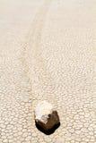 Moving rock on cracked desert ground Stock Photos