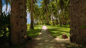 Moving through rustic gates to park with palm trees on lawn grass, Philippines. Camera moving through rustic gates to park with palm trees on lawn grass stock video