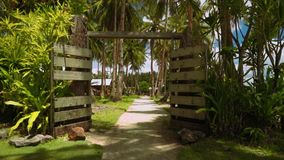 Moving through rustic gates to village with palm trees on lawn grass. Camera moving through rustic gates to village with palm trees on lawn grass, Philippines stock video footage