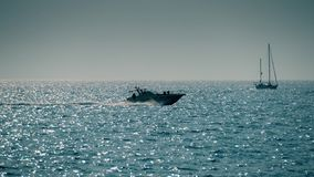 Moving sailboat and motorboat in the sea. Moving sailboat and fast motorboat stock images