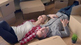 Moving,shifting, repairs, new keys to the apartment. Couple girl and the guy holding the keys to the apartment while man. And woman lying on the floor among the stock video footage
