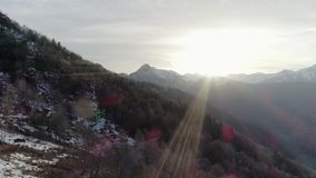 Moving side over bare fall woods forest and snowy mountain in autumn or winter day. Outdoor sunny nature scape rocky stock video footage
