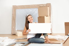 Moving sign woman. Woman moving in new home unpacking showing blank white sign while doing furniture assembly of new table. Beautiful young mixed race Asian Stock Photo