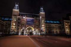 Moving silhouettes of cyclists and passersby near Rijksmuseum. Royalty Free Stock Photo