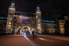 Moving silhouettes of cyclists and passersby near Rijksmuseum. Stock Images