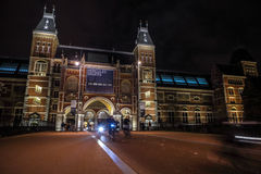 Moving silhouettes of cyclists and passersby near Rijksmuseum. Royalty Free Stock Photos