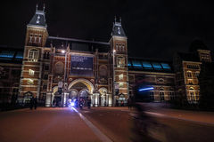 Moving silhouettes of cyclists and passersby near Rijksmuseum. Stock Photos