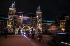 Moving silhouettes of cyclists and passersby near Rijksmuseum. Royalty Free Stock Image