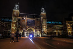 Moving silhouettes of cyclists and passersby near Rijksmuseum. Royalty Free Stock Images